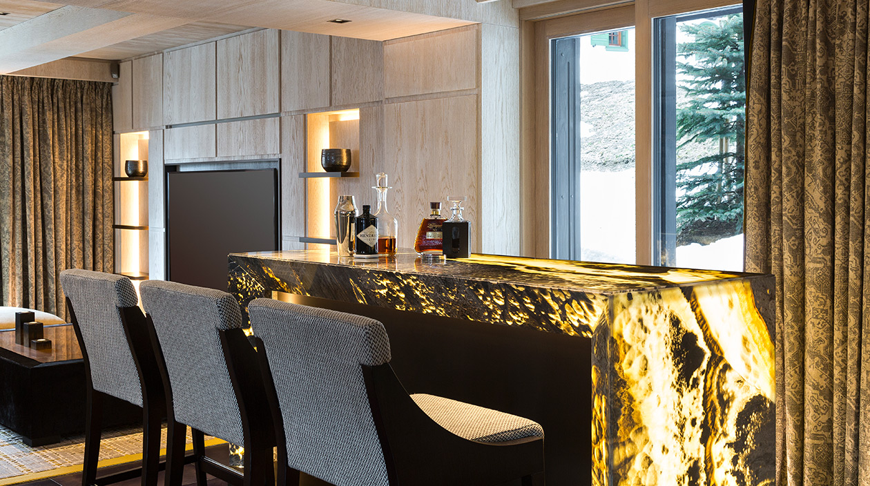 Sybille de Margerie - French interior designer - Chalet A, located in Courchevel 1850 - contemporary chalet - Bar stools grey - Backlit natural stone bar - Signatures Singulières magazine - The digital magazine of French talent